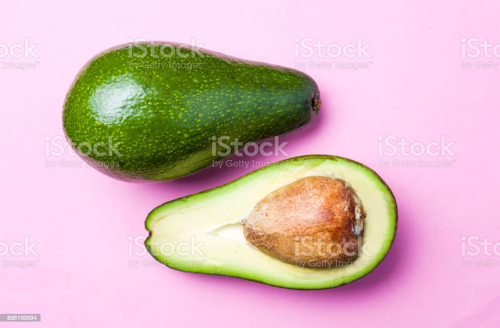 Avocado slices on pink background stock photo