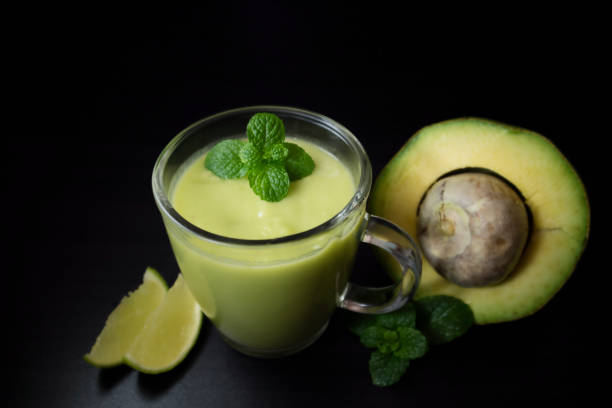 Avocado smoothie withi mint and lime on dark background with copy space for text. Selective focus. Healthy food concept. stock photo