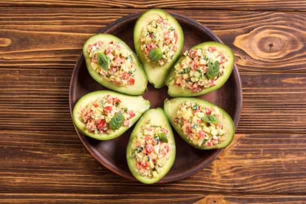 用黃瓜、番茄和雞蛋填充的鱷梨 - 塞滿的 個照片及圖片檔