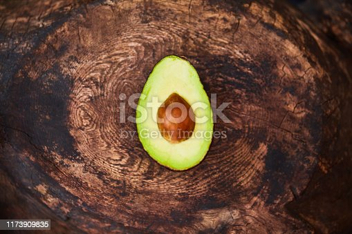 High angle shot of an avocado cut in half on a wooden table