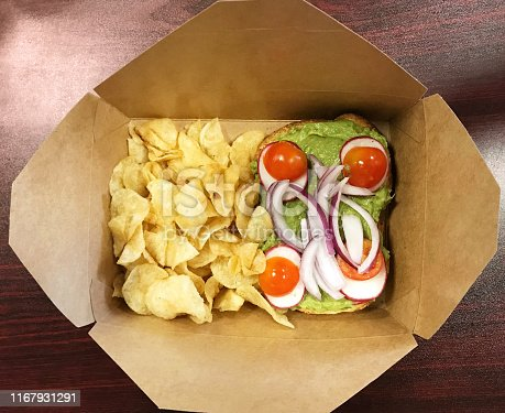Avocado toast and chips in a take out box