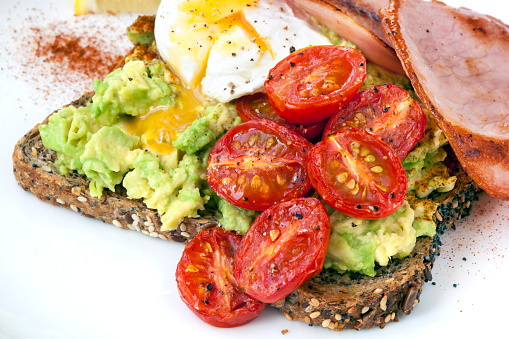 Avocado Toast with Cherry Tomatoes Poached Egg and Bacon Top View