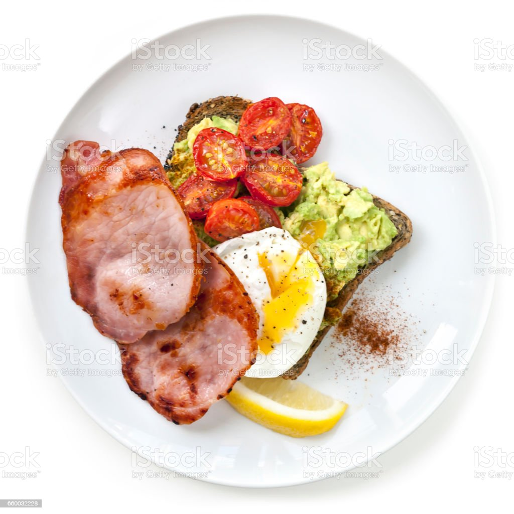 Avocado Toast with Cherry Tomatoes Poached Egg and Bacon Top View stock photo
