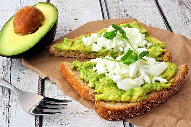 Avocado toast with egg whites and pea shoots Avocado toast with egg whites and pea shoots on paper against a white wood background egg white stock pictures, royalty-free photos & images