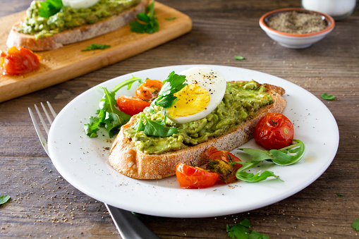 Avocado toast with roasted tomatoes and eggs, on a white plate on a rustic wooden table.  Served with fresh arugula and sprinkled with parsley and black pepper. Stock photo.