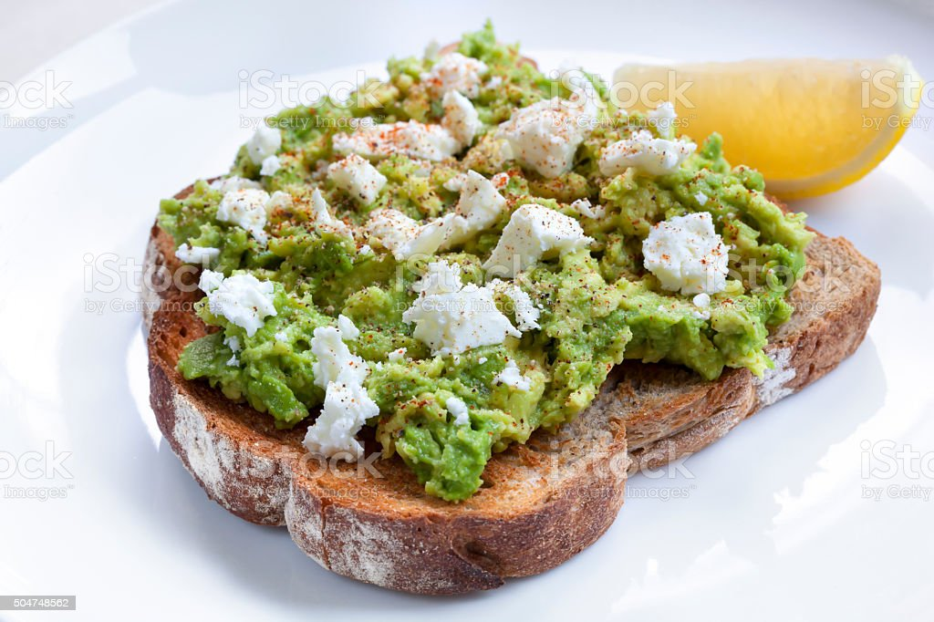 Avocado Toast with Feta Cheese Lemon and Spices stock photo