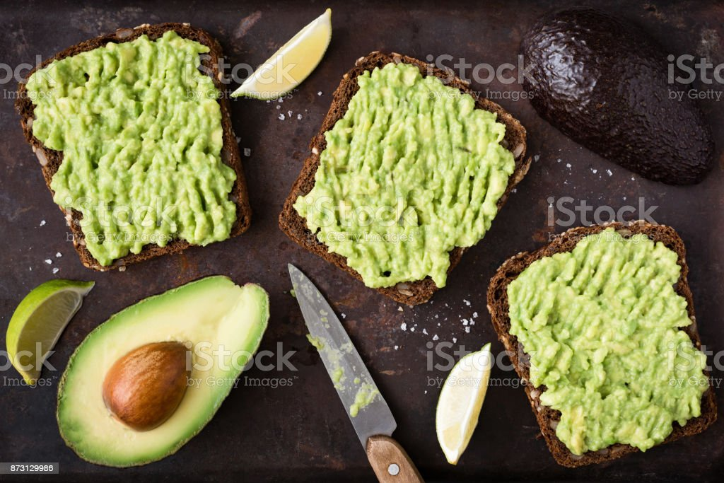 Avocado toast with whole grain rye bread. Top view stock photo