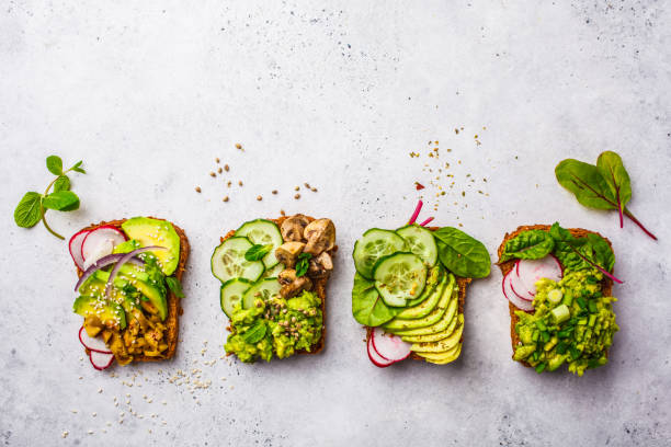 Avocado toasts with different toppings, top view, white background, copy space. stock photo