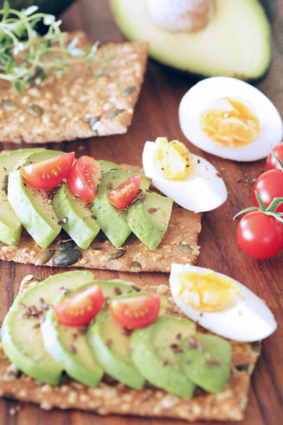 Avocado, tomato and boiled egg on pumpkin seeded crackers - shallow dof stock photo