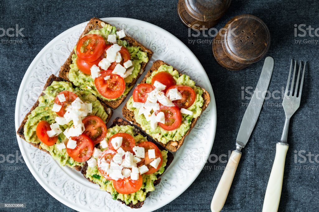 Avocado, tomato and cheese on toasted bread. Healthy snack, appetizer stock photo