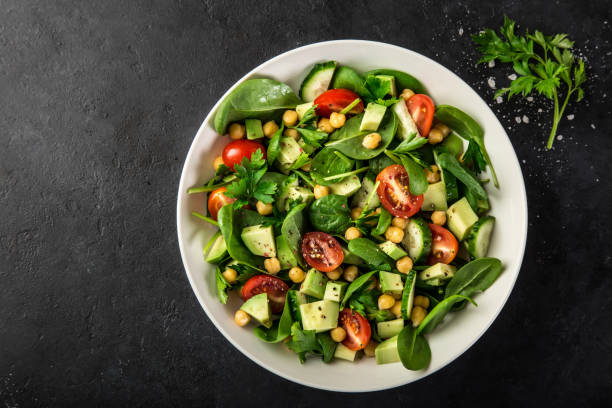 Avocado, tomato, chickpeas, spinach and cucumber salad stock photo