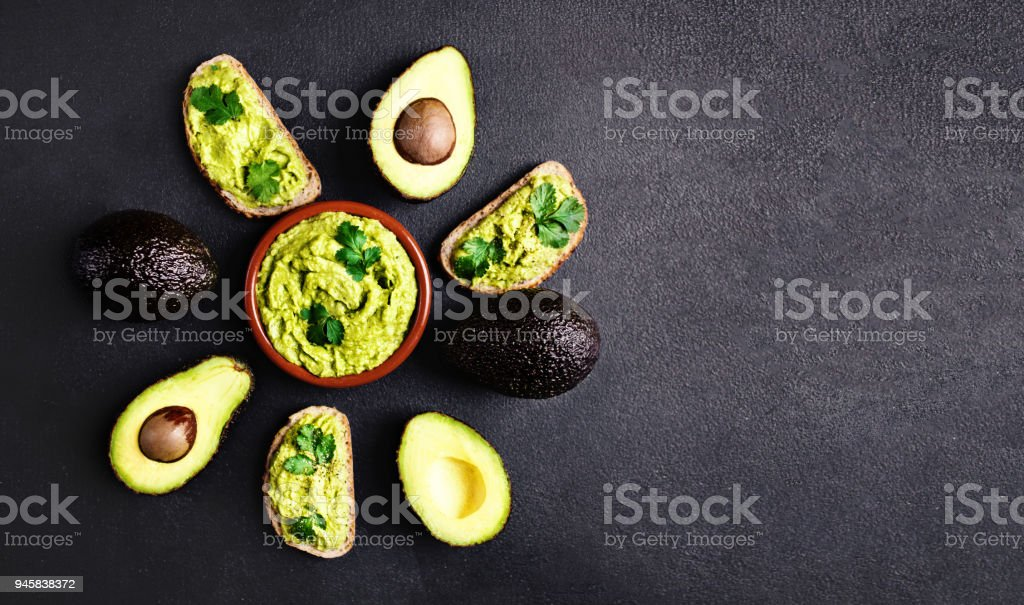 Avocado with guacamole sauce in a bowl on black background, top view. Whole and Half of avocado. Guacamole ingredients. stock photo