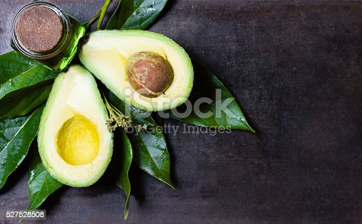 istock Avocado with leaves on black background. top view 527528508