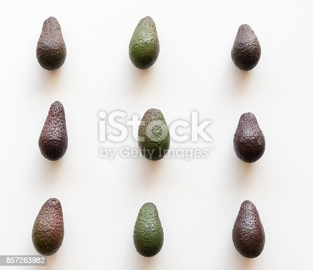 High angle view of organic green and black Hass avocadoes arranged on white table background