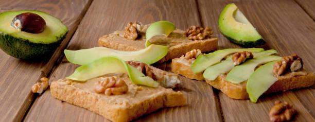 avocados und toaster mit erdnusspaste auf holzhintergrund. hausgemachte leckere und gesunde frühstücks-toast - ofengemüse mit feta stock-fotos und bilder