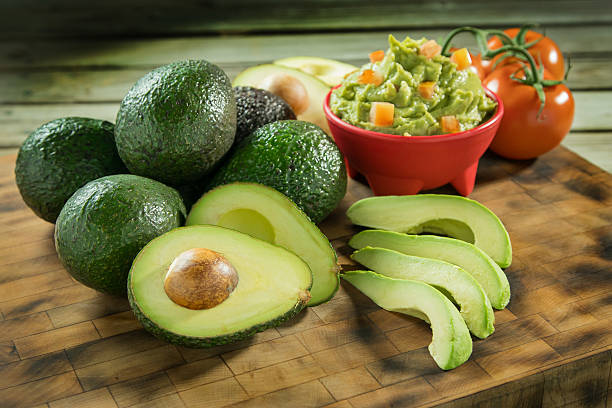 Avocados and tomatoes on a cutting board stock photo