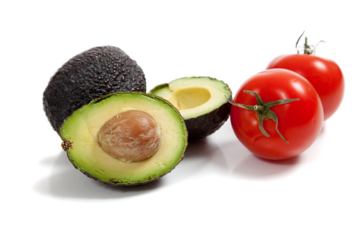 Avocados and tomatoes on white
