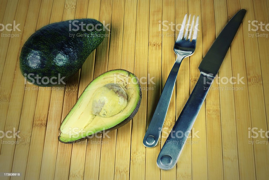 Avocados with knife and fork effect stock photo