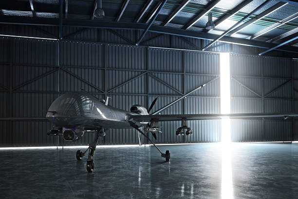 Awaiting flight. Lone drone U.A.V aircraft awaiting a military mission in a hanger. 3d model scene. airplane hangar stock pictures, royalty-free photos & images