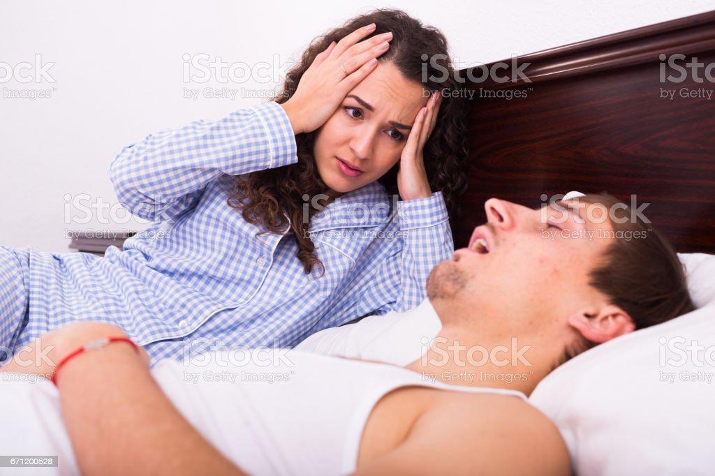 Awake woman watching snorring husband at night stock photo