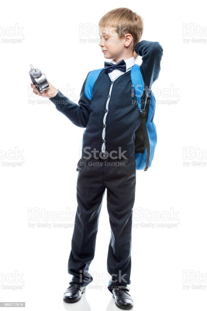awakened schoolboy watching time on the alarm clock, portrait isolated zbiór zdjęć royalty-free