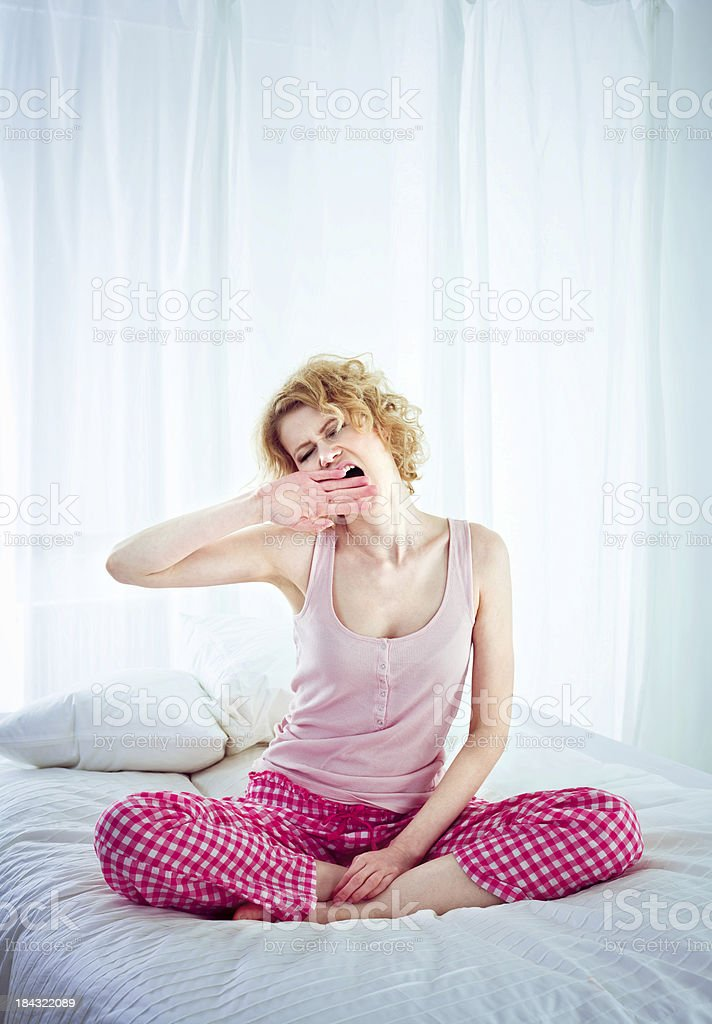 Awakening Young adult woman wearing pajamas sitting cross-legged on the bed in a bedroom and yawning.  25-29 Years Stock Photo