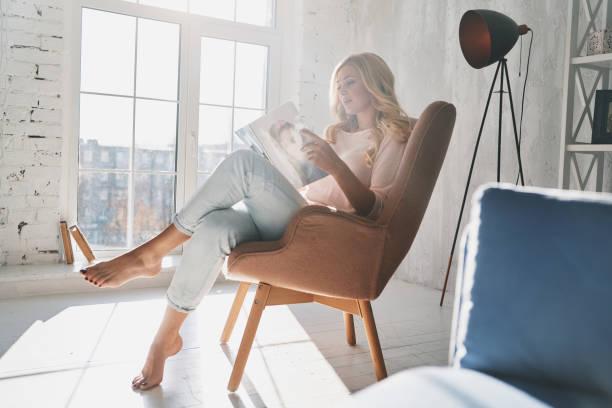 de hoogte van het laatste mode nieuws. - woman home magazine stockfoto's en -beelden
