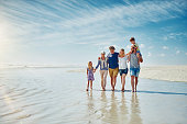 Shot of a happy family going for a walk together at the beach
