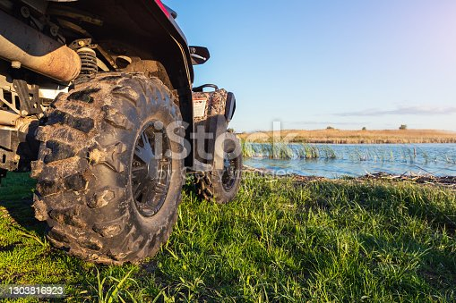 istock ATV awd quadbike motorcycle pov view near lake or river pond coast with beautiful nature landscape sky background. Offroad travel adventure trip expedition. Extreme sport recreation activity 1303816923