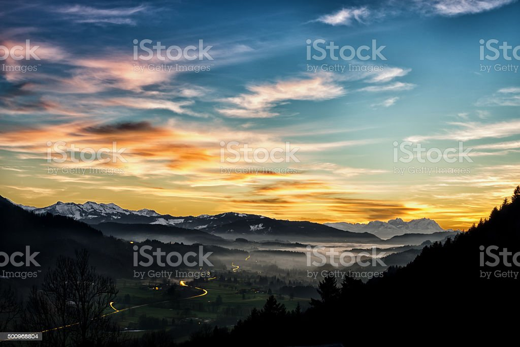 Awe alpine sundown with fog and car light trails stock photo