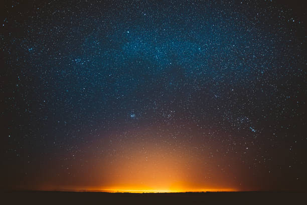 Awe Beautiful Night Sky Glowing Stars Background Backdrop With Colorful Sky Gradient. Sunset Sunrise Light And Colourful Night Starry Sky In Blue Yellow Orange Colors stock photo
