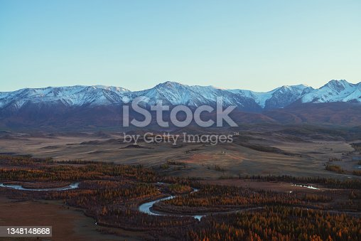 istock Awesome autumn landscape with mountain river in forest valley and great snow-covered mountain range in red sunset sunshine. Spectacular view from hill to snowy mountains and autumn valley in sunlight. 1348148668