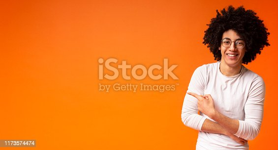 istock Awesome black guy in glasses pointing away at copy space 1173574474