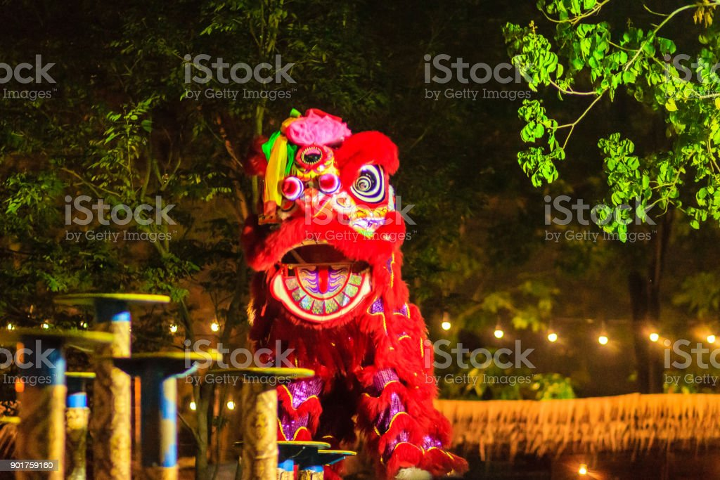 Awesome Chinese lion dancing shows on the poles at night during Chinese new year festival in Bangkok, Thailand. Shot with high ISO with noise grain and blurred stock photo