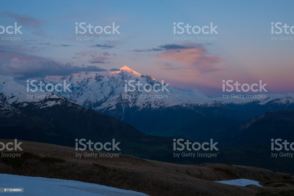Awesome colorful sunset over snow-capped mountain peak stock photo