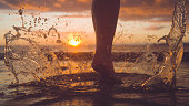 CLOSE UP Awesome crystal clear water splashing as woman runs into sunlit ocean. Breathtaking burnt orange sun rays illuminate unrecognizable girl running into the vast ocean. Stunning evening seascape