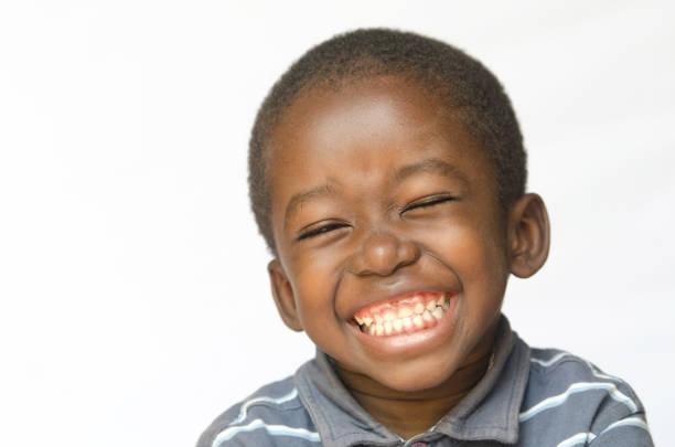 Awesome enorme glimlach op zwarte Afrikaanse etniciteit zwarte jongenskind geïsoleerd op wit portret foto