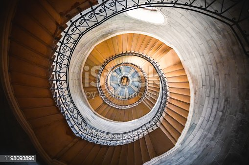 Architecture of a large spiral staircase with beautiful sunlight from outdoor, seen from below inside one of the bell towers of the Basilica Notre Dame de Fourviere. The Basilica was built between 1872 and 1884 with Byzantine and Romanesque architecture style, in a dominant position overlooking the city of Lyon, and dedicated to the Virgin Mary. It features fine mosaics and superb stained glass very ornate with gold and some paintings on the ceiling. This image was taken inside this famous place of worship monument in Lyon city, in Rhone department, Auvergne-Rhone-Alpes region in France (Europe), on Fourviere hill.