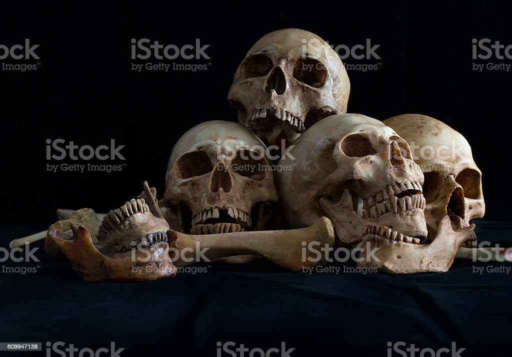 Awesome pile of skull and bone on black cloth stock photo