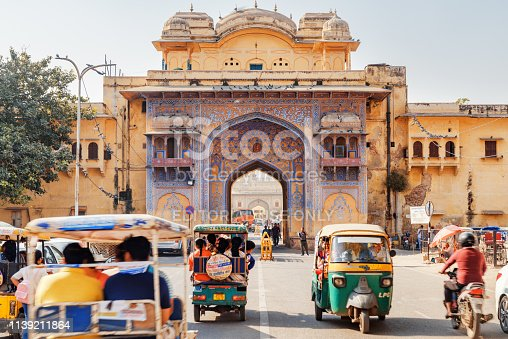 Jaipur, India - 11 November, 2018: Awesome view of scenic gate on Tulsi Marg at Gangori Bazaar. Tourists and residents walking along the Old Pink City. Day traffic. Cars, motorbikes and auto rickshaws