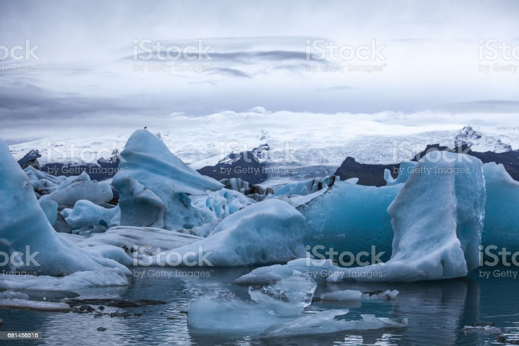 Awesome view over the glacier with a lot of ice rocks in the lake in front. Mountain range with snow in the background. Light and shadow. Cold water and tough wind in the nature. royalty-free stock photo