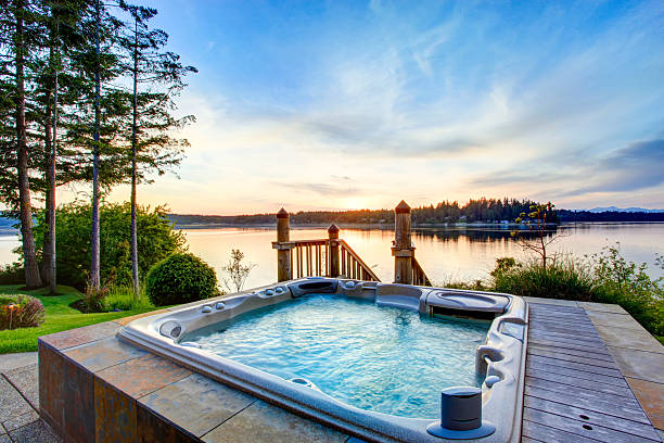 awesome water view with hot tub in summer evening. - whirlpool terrasse stock-fotos und bilder