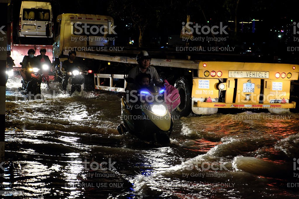 Awful flooded street, motorcycle swim in tide stock photo