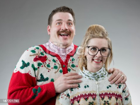 A couple of people dressed in their best ugly sweater, posing for a christmas photo.