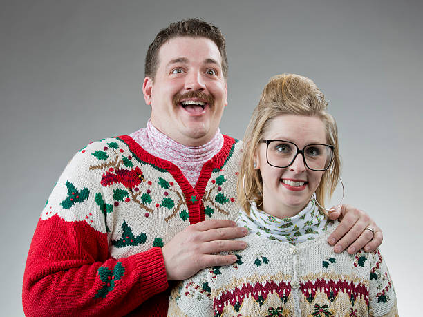Awkward Christmas Photo A couple of people dressed in their best ugly sweater, posing for a christmas photo. ugliness stock pictures, royalty-free photos & images