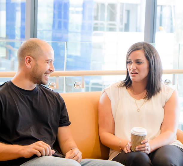 Awkward conversation among coworkers - man thinks he's funny, but the woman is offended - candid image of real people stock photo