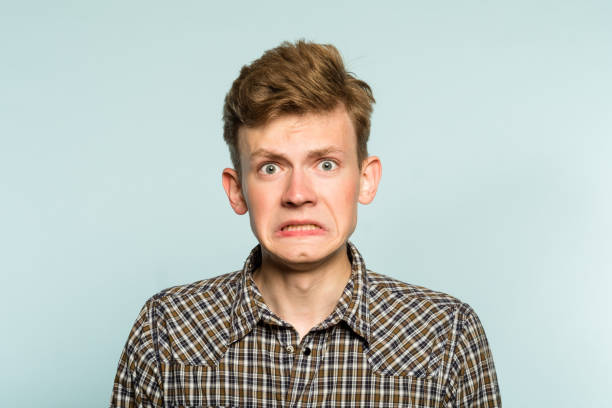 awkward gawky fumbling dorky man facial expression awkward gawky fumbling oafish dorky man facial expression. portrait of a young guy on light background. emotion facial expression. feelings and people reaction. embarrassment stock pictures, royalty-free photos & images