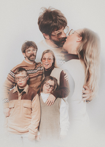 A Caucasian family poses for a portrait in the style of the late 1970's or early 1980's.  They wear matching brown and tan outfits.  The father and mother appear to be kissing or making out, a bit uncomfortable in the context.