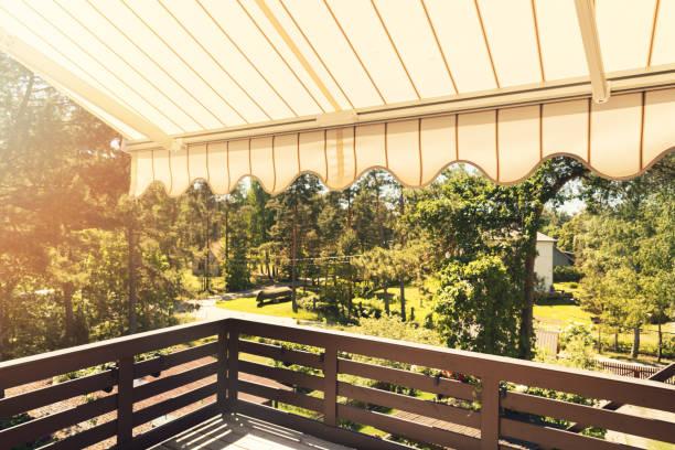 markise über balkon-terrasse am sonnigen tag - outdoor sonnenschutz stock-fotos und bilder