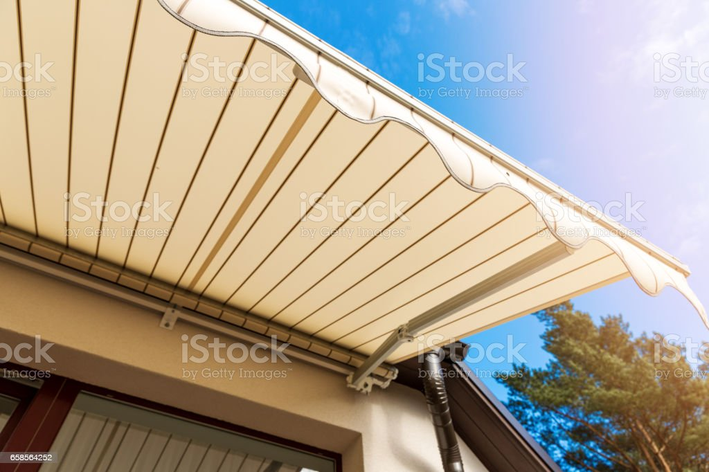 awning over balcony window against blue sky stock photo